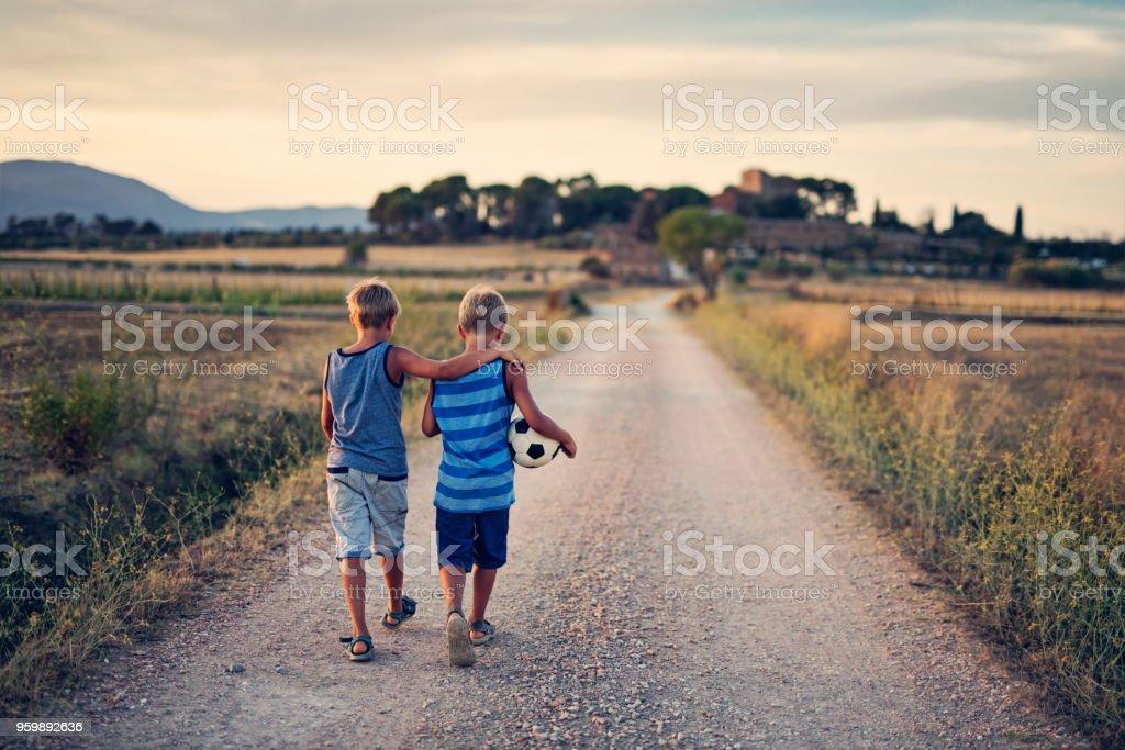 Hermanos gemelos regresar a casa después de jugar al fútbol. - foto de stock