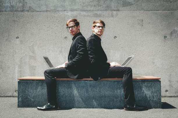 twin brothers shoulder on shoulder working twin brothers with black suits and glasses sitting in urban surrounding shoulder on shoulder with their laptops and working global wireless. samenwerking stock pictures, royalty-free photos & images