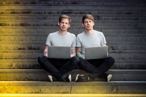 Zwillingsbrüder mit Laptops sitzt auf der Treppe – Foto