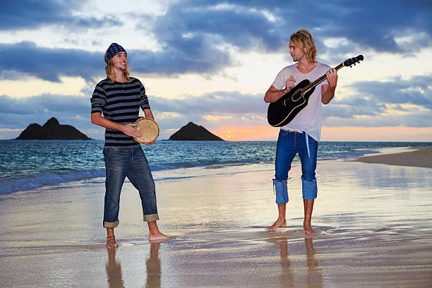 twin brothers with their guitar and drum at sunrise stock photo