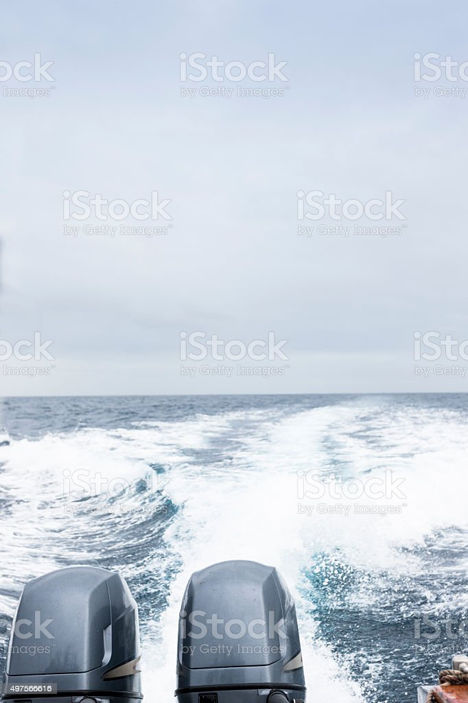 Twin engines roaring through the ocean creating a wake stock photo