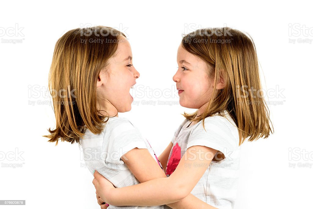 Twin girls are looking at eachother and smiling. stock photo