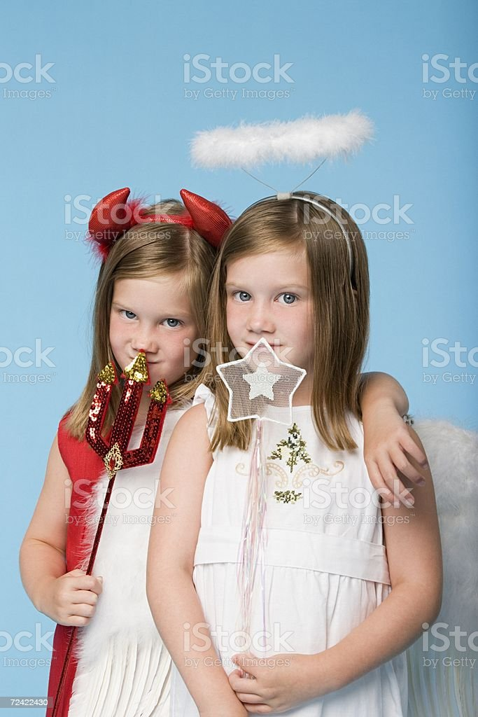 Twin girls dressed as an angel and devil royalty-free stock photo