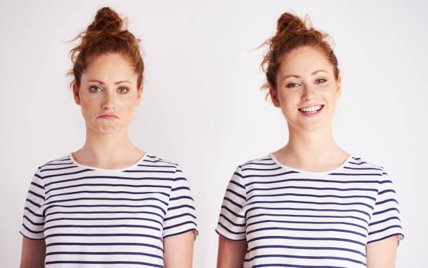 zwillingsmädchen in verschiedenen stimmungen - zwillinge stock-fotos und bilder