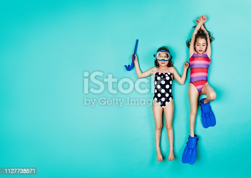 Two girls lying down with snorkelers and flippers. Top view of twin girls wearing swimwear on blue background.