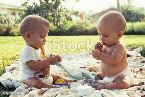 A horizontal image shows 2 female infants about 6 months of age.  They are sitting, facing each other, but are engrossed in their hands. It is a sunny day and they are sitting in the shade.