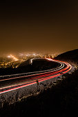 View from Twin Peaks in San Francisco at night. Showing the windy road with car light trails going around a scenic bend in the road.