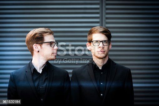 twin brothers with black suits and glasses.