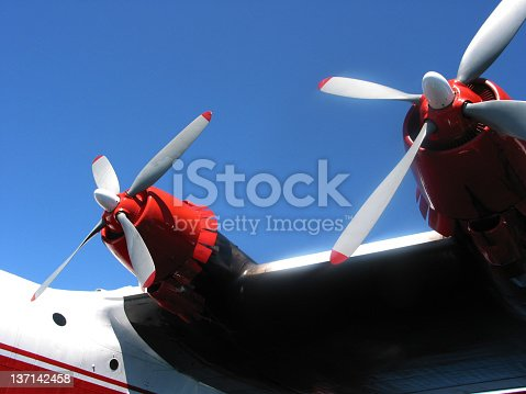 Two, red-tipped propellers of a Martin Mars Water Bomber airplane used for fighting forest fires. Taken at Sproat Lake, Port Alberni, British Columbia.