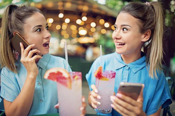 zwillingsschwestern sind cocktails trinken und reden mit ihren freunden über mobiltelefon - zwillinge stock-fotos und bilder