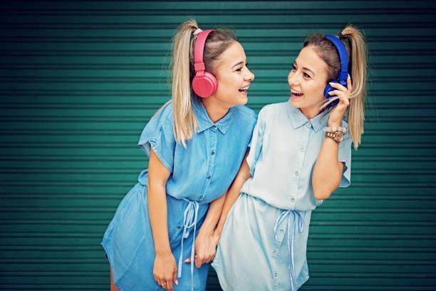 zwillingsschwestern mit drahtlosen kopfhörern musik hören und machen spaß - zwillinge stock-fotos und bilder