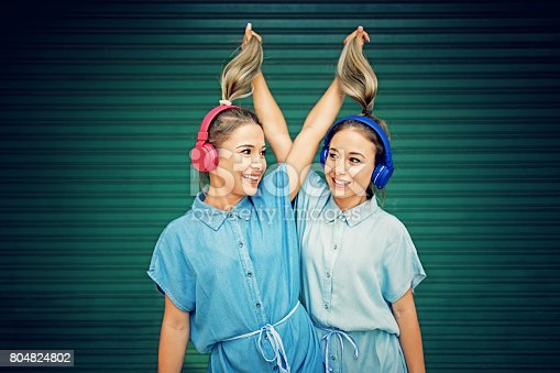 Twin sisters are making fun and pulling their ponytails each other till listening the music