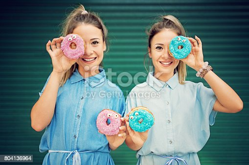 692840848istockphoto Twin sisters are making fun with colorful donuts 804136964