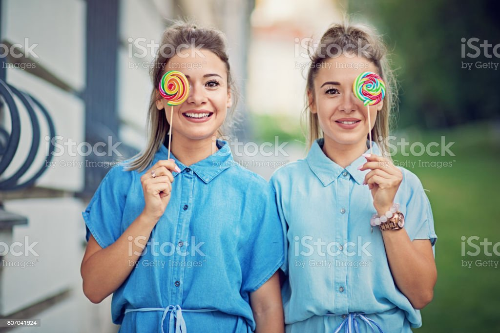 Twin sisters are making fun with colorful lollipops stock photo