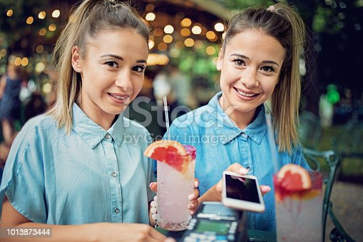 Twin sisters are paying their cocktails using mobile phone