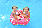 Twin sisters at Christmas sit in a swim ring in the swimming pool and fill