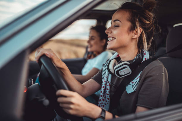 Twin sisters driving car and enjoying road trip stock photo