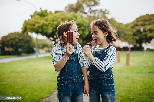 Two little twin sisters in identical clothes standing outdoors and eating chocolate ice cream candy. Two little girls enjoying eating candy icecream outdoors.