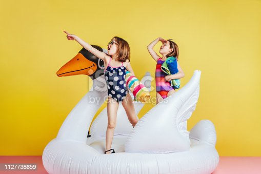 Cute girls having fun on inflatable toy flamingo over yellow background. Girl friends in swimsuits holding towels pointing and looking away.