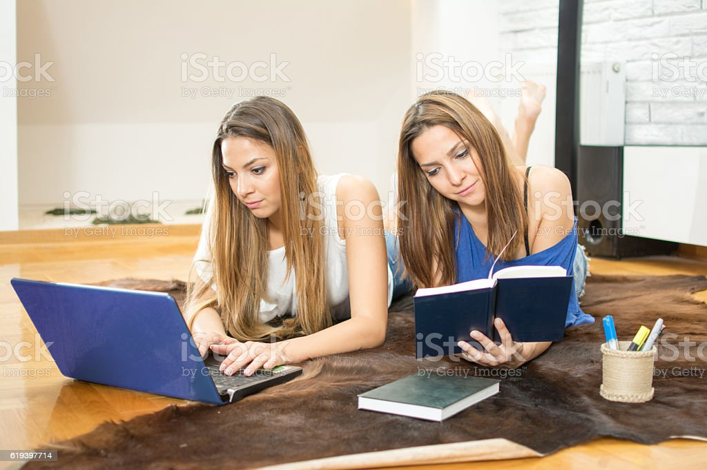 Young sisters preparing for exams using laptop and books in apartment...