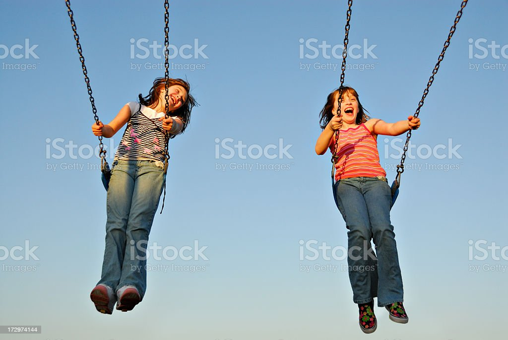 A twin sisters swinging happily on a sunny day royalty-free stock photo