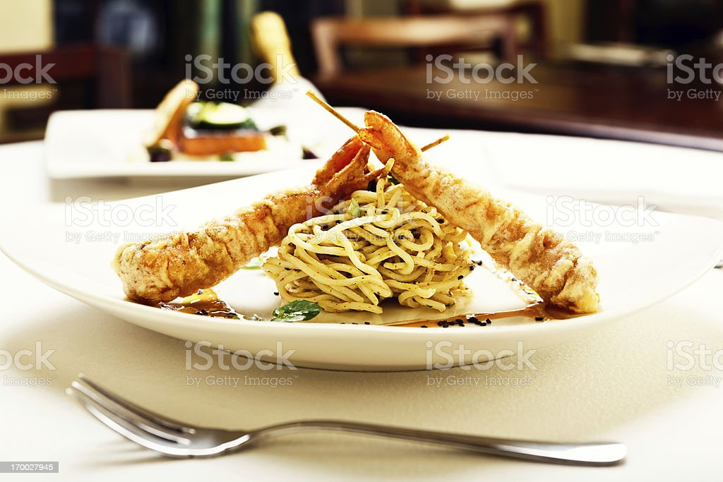 Twin tempura prawns with crispy noodle nest in elegant restaurant royalty-free stock photo