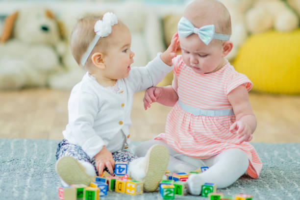 Twin Toddlers Playing Together stock photo