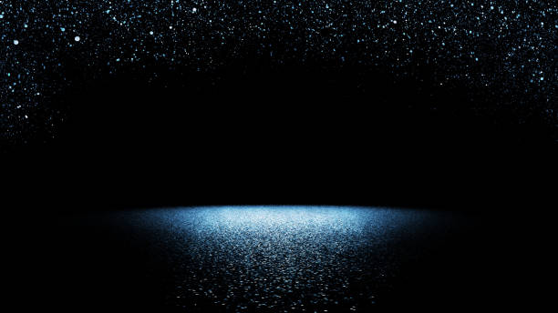 twinkling blue glitter falling on a flat surface lit by a bright spotlight stock photo