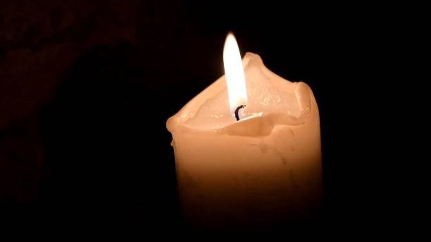 Twinkling candle flame in darkness. Remembrance concept. Day of mourning stock photo