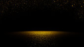 twinkling golden glitter falling on flat surface lit by spotlight