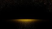 twinkling golden glitter falling on flat surface lit by spotlight