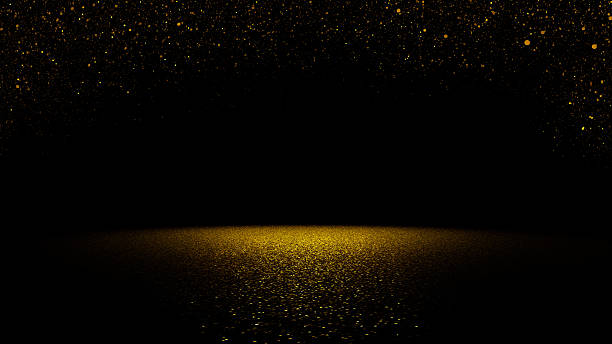 twinkling golden glitter falling on flat surface lit by spotlight stock photo