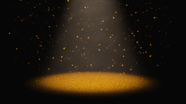 twinkling golden glitter falling through a cone of light on a stage stock photo