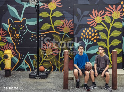 Twin brothers of Chinese  ethnicity posing with basketball while sitting at the alley basketball court featuring large mural on the wall behind. Urban city setting of North American city.