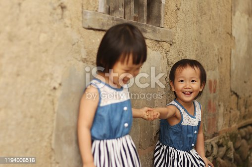 two Asian twins girls hand in hand walking and playing in front of a old house with mottled olden wall