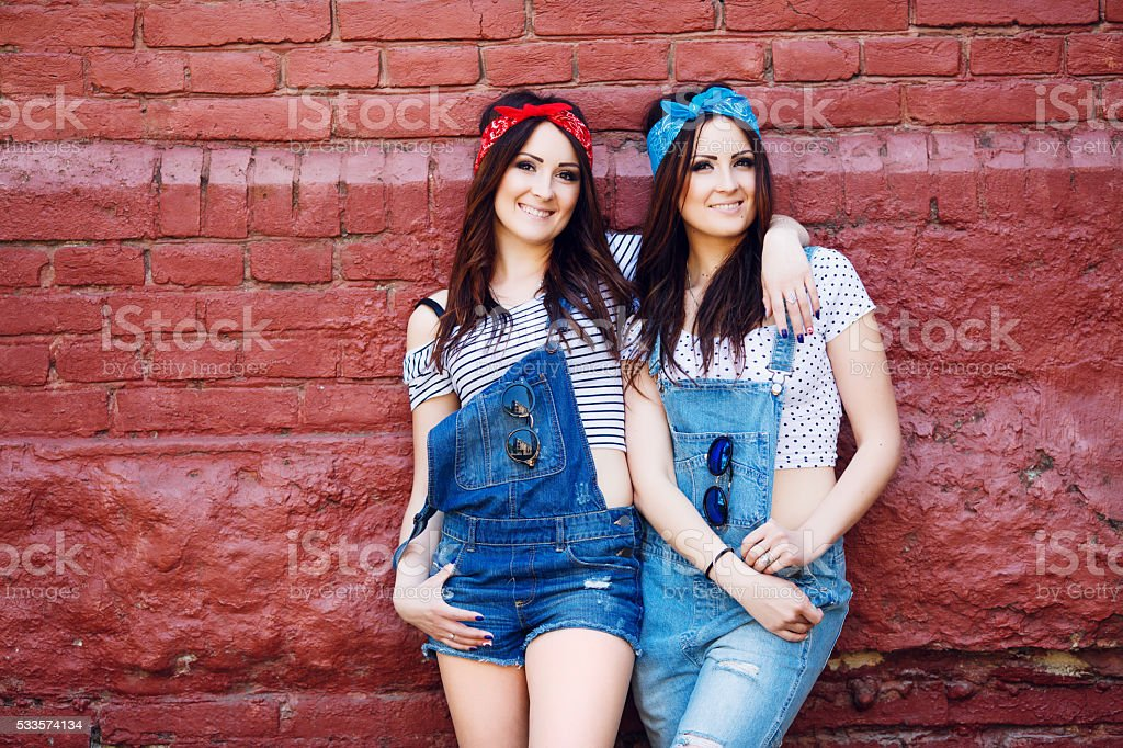 twins girls hugging front of the urban wall stock photo