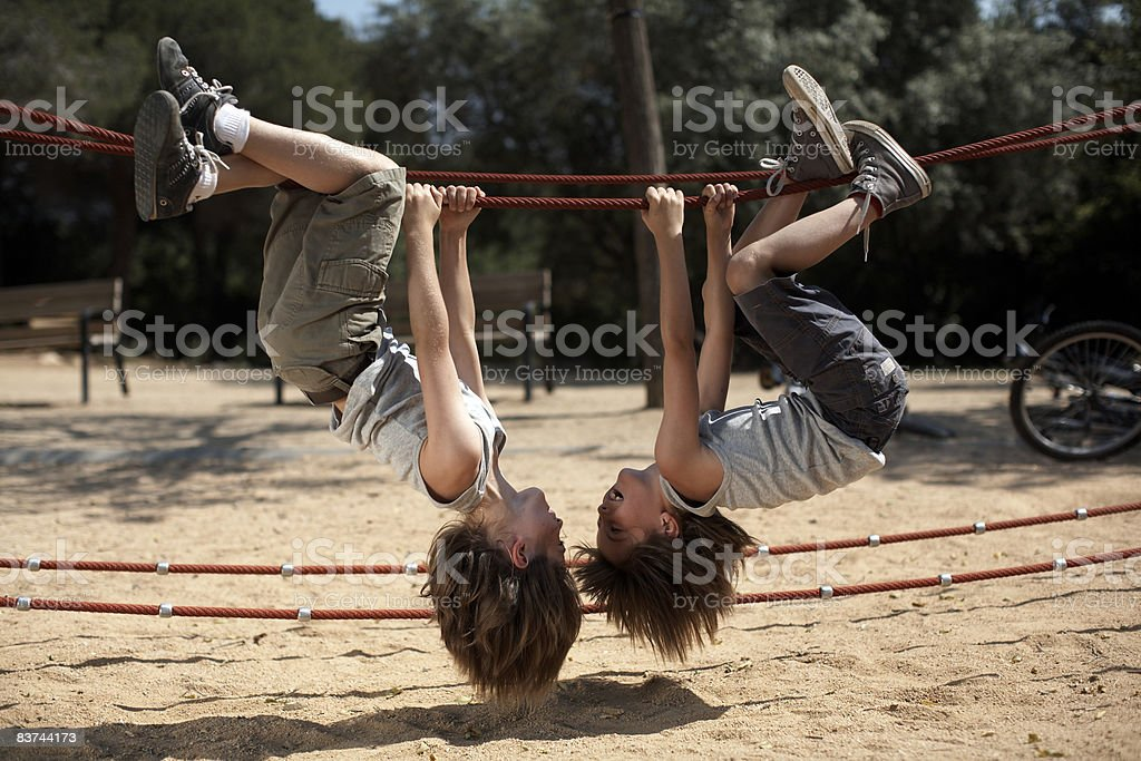 twins hang from structure in park royalty-free stock photo