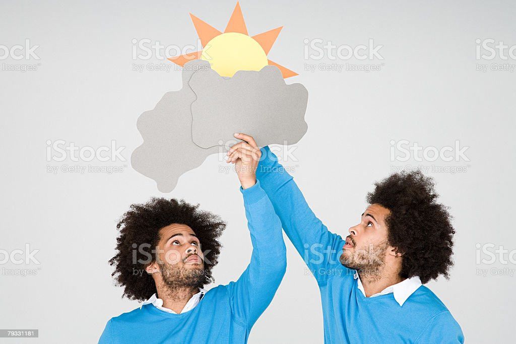 Twins holding a card sun and clouds royalty-free 스톡 사진