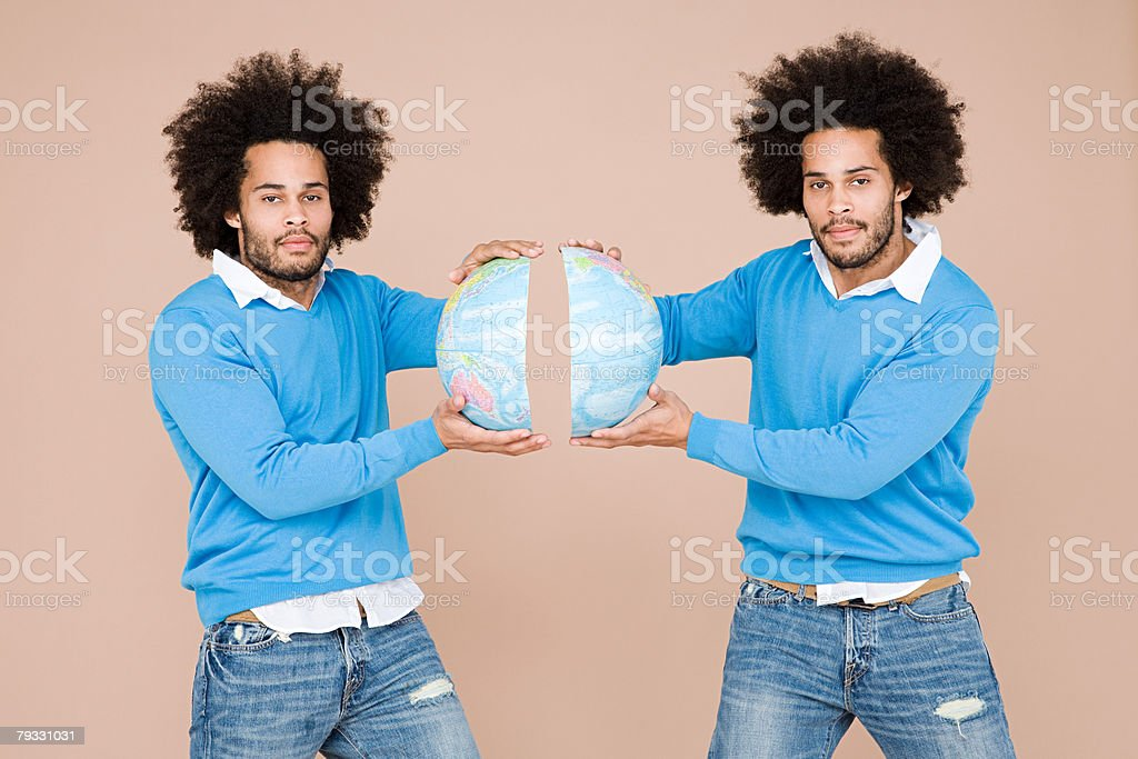 Twins holding two halves of the earth stock photo