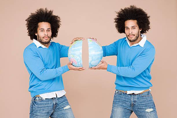 twins holding zwei teile der welt - zwillinge stock-fotos und bilder