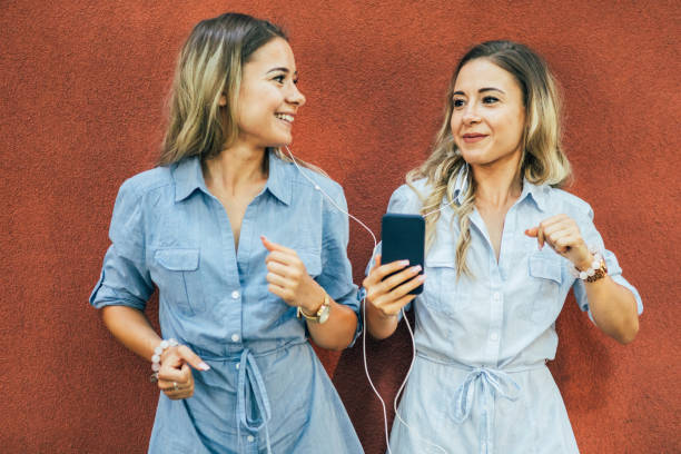 Twins listening to music stock photo