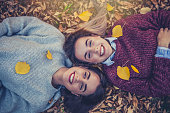 17 years old twins are lying down at the public park. They are enjoying in autumn days