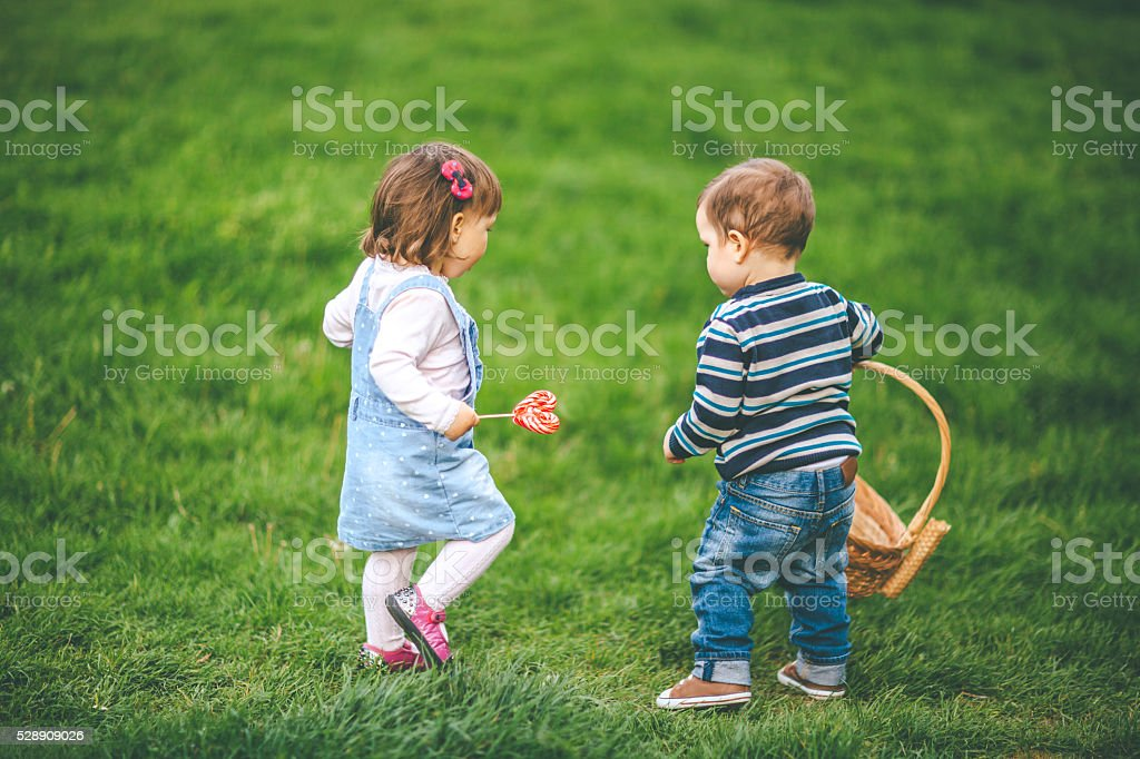 twins playing on meadow stock photo