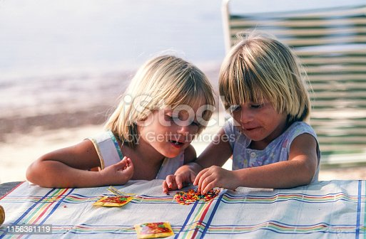 A horizontal image during daytime near a beach shore. Twin girls about 4 years of age are engaged in looking at their candy on the picnic table. There's a table cloth over the wood table. The girls are blonde and there is room for copy space