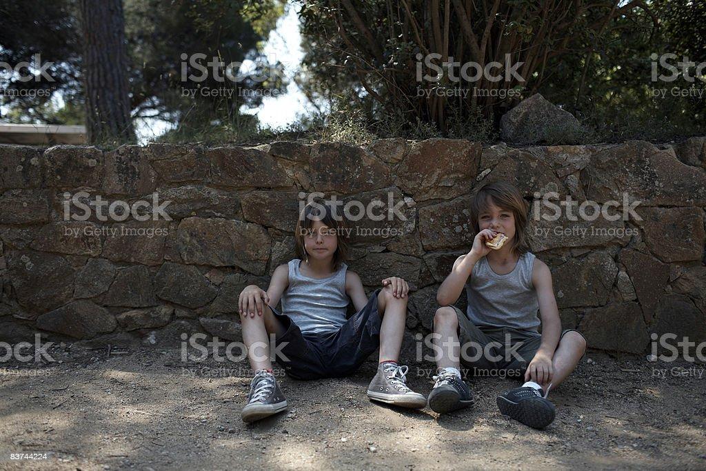 Bliźniaczki siedzieć w parku jedzenie zbiór zdjęć royalty-free