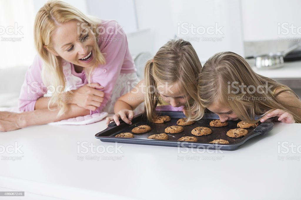 Twins smelling fresh homemade cookies royalty-free stock photo