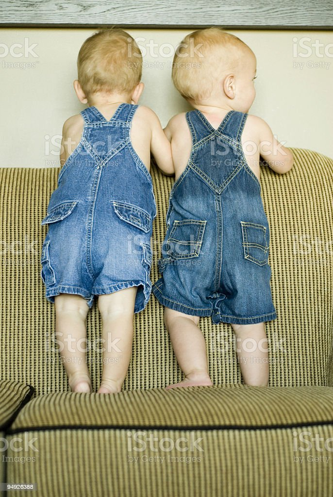 Twins standing on a sofa together royalty-free stock photo