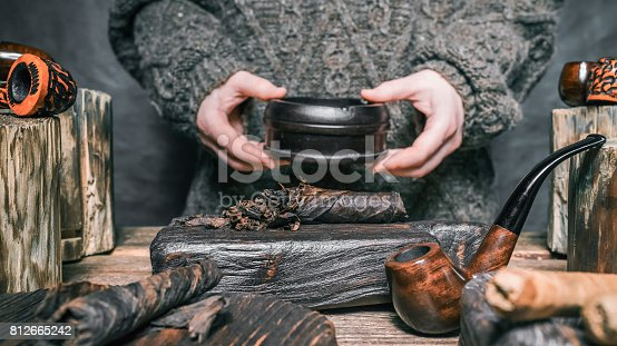 Human hands holding ashtray above sliced twist tobacco. Tobacco and pipes on wood stands and boards. Close-up front view