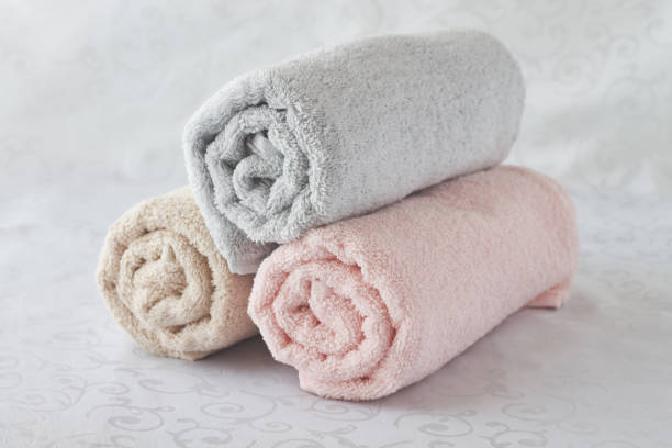 twisted bath towels on white background - sauna textilien stock-fotos und bilder