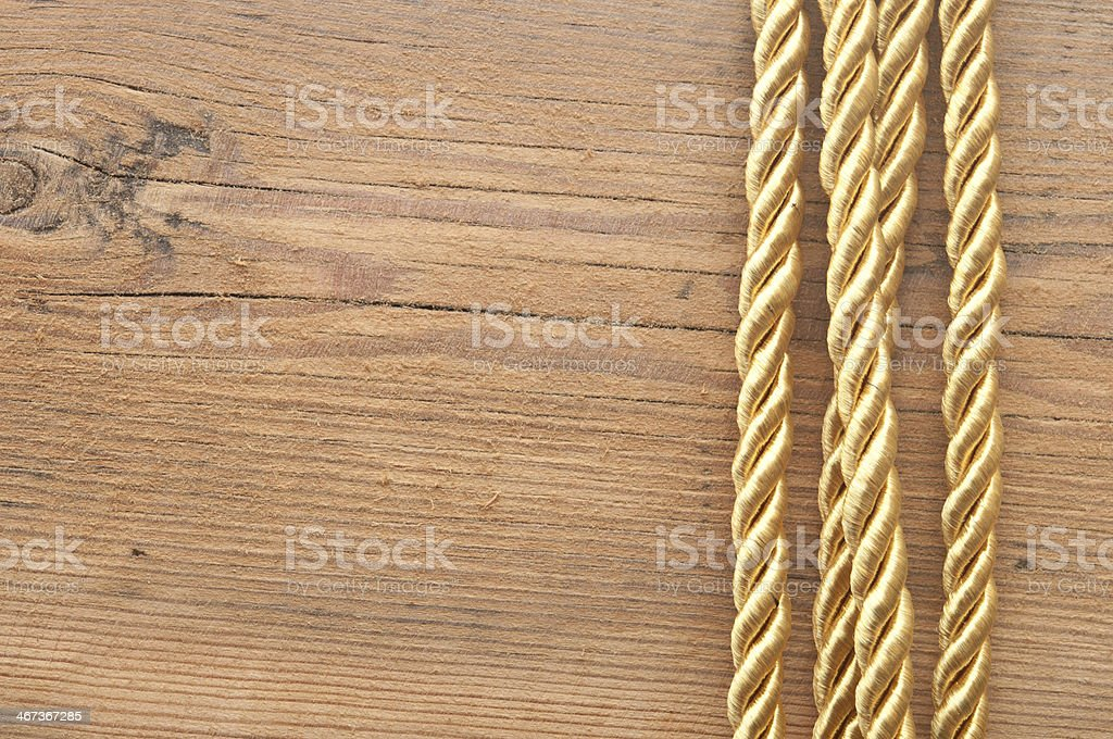 Twisted gold rope on wooden background stock photo